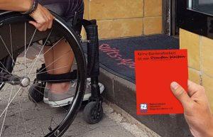 Rollstuhlnutzerin vor einer Stufe vor einer Apotheke mit Roter Karte